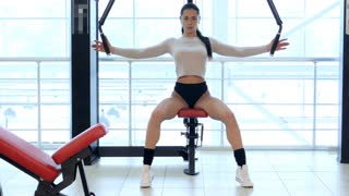Girl athlete trains the chest muscles in the gym