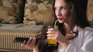 Girl drinking juice and watching television smiling