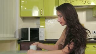 Girl in the kitchen drink coffee