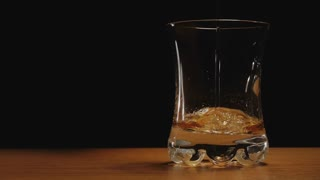 Liquor or whiskey poured in a glass against black background