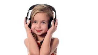 Little girl listening to music on headphones