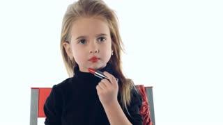 Little girl makes up lips