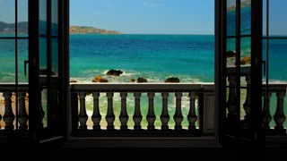 Looking out the window to the balcony and the sea