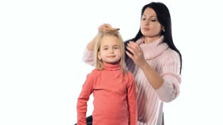 Mother combing hair daughter