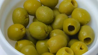 Pickled green olives in a bowl on a white background