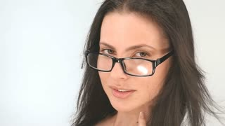 Portrait of a girl with long hair, she poses in glasses on a white background, slow motion,100fps