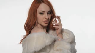 Red-haired girl posing in a white fur coat