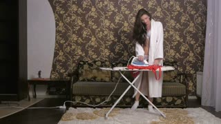 The girl irons clothes iron and dancing