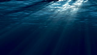 Dark blue sea surface seen from underwater.  Abstract waves underwater and rays of sunlight shining through.
