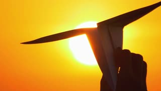 10 in 1 video! The hand hold paper airplane by the bright sun (sunset) background. Slow motion and real time capture. Shot with Red Cinema Camera