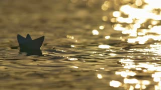 2 in 1! The toy paper boat on the surface water by the bright sunlight background