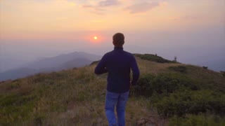 2 in 1 video! The man run in the mountain on the background of the sunset. Slow motion. Wide angle