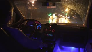 2 in 1 video! The man sit in a car in the rainy city. Inside view. Evening-night time
