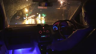 2 in 1 video! The man sit in a car in the rainy city with left hand traffic. Inside view