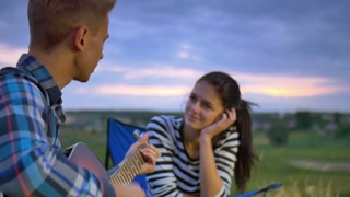 3 in 1 video! The couple (pair) sit near bonfire and camping tent: the man play on the guitar and woman drink tea and smile. Shot with Red Cinema Camera and crane