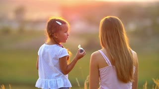 3 in 1 video! The mother and daughter on the rest: girl blow air bubbles and sing by landscape background. Slow motion capture. Shot with Red Cinema Camera