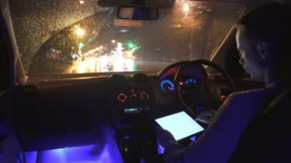 4 in 1 video! The man use the tablet in a car in the rainy city. Inside view. Night time