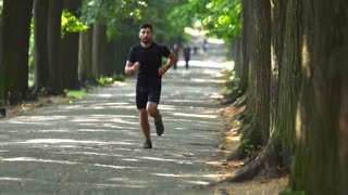 4 in 1 video! The sportsman run on the beautiful park alley. Slow motion. Super telephoto lens shot