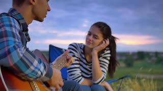 5 in 1 video! The couple (pair) sit near bonfire and camping tent: the man play on the guitar and woman drink tea and smile. Shot with crane and Red Cinema camera