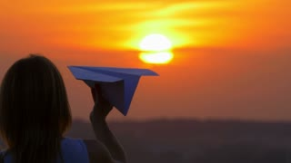 5 in 1 video! The hand hold paper airplane and launch by the bright sun background. Slow motion capture. Shot with Red Cinema Camera