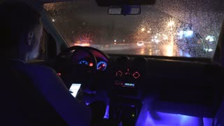 5 in 1 video! The man use the phone in a car in the rainy city. Inside view.Night time