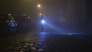 6 in 1 video! The man inspect a street with a flashlight in his hand on a dark background. Evening-night time, foggy weather, real time capture