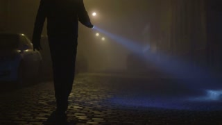6 in 1 video! The man with a flashlight in his hand, inspecting cars on the street. Evening-night time, foggy weather, real time capture