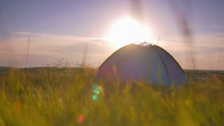 Man stand near camping tent on the hill by picturesque landscape background