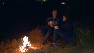 Pair sit and drink tea, kiss and talk in the camping tent