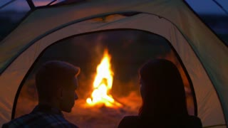 Pair sit, drink tea, talk, kiss and laughter in the camping tent