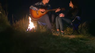 Pair sit near bonfire and camping tent: man play the guitar