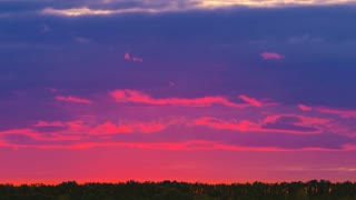 The bright sunset against the background of cloud stream. Time lapse. Wide angle