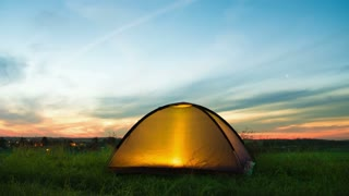 The camping tent by sunset (sunrise) background