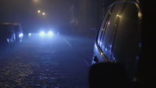 The car on a dark background of the approaching headlights. Evening-night time, foggy weather, real time capture