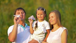 The family (father, mother and daughter) hold and launch paper airplane