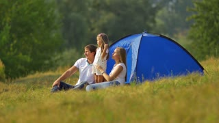 The family (father, mother and daughter) sit near tent on the hill by forest background. Real time capture. Shot with Red Cinema Camera