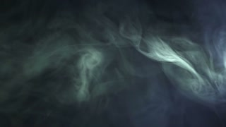 The flow of smoke on the dark background. Slow motion capture
