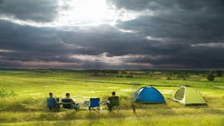 The friends set up camp, tent and cook food by sunny and cloudy picturesque landscape background