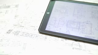 The hand work with tablet (ipod) by blueprints engineering project background