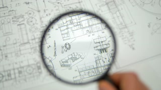 The look through loupe (magnifier) at blueprints engineering project
