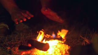 The man sit near bonfire and heat hands. Close up view