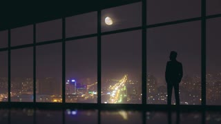 The man stand at the panoramic window on the background of night the city. Time lapse. Wide angle
