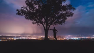 The man stand near the tree against the background of the night city. Time lapse