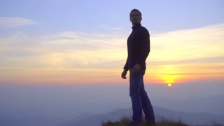 The man stand on the mountain against the background of sunset. Real time capture. Wide angle