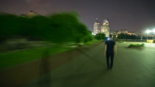 The man walk along the promenade in the night city. Time lapse (Hyperlapse). Wide angle