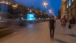 The man walk on the street in the evening city. Time lapse (Hyperlapse). Wide angle