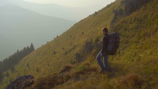 The man walk with a backpack in the mountain. Real time capture. Wide angle