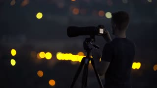The man work with a camera on the background of night city light. Real time capture