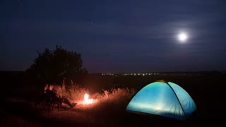The people sit and stand near camping tent and bonfire by picturesque sky