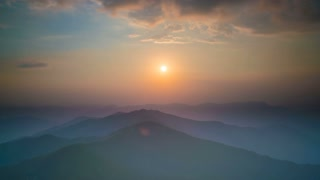 The picturesque mountain view on the the background of the sunrise. Wide angle. Time lapse